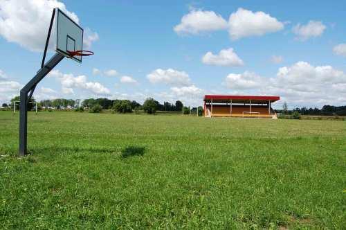 """Kaip ir daugumoje panašių miestelių, akivaizdžios pastangos stadionus paversti """"multifunkciniais sporto maniežais"""", kas dažniausiai išreiškiama šalia futbolo aikštės įrengta krepšinio aikštele. Šiuo atveju, vieniši pievoje stūksantys krepšiai dar aikšiau byloja apie liūdną šio komplekso dalią nei apžėlęs futbolo laukas."""