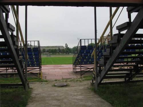 Žvilgsnis pro abi tribūnas link aikštės. Keistų įpročių, kurie būdingi tribūnų statytojams Jonavoje nekomentuosiu - nors stebėtis yra dėl ko, nes, atrodo, abi tribūnos yra iš esmės tokių pačių konstrukcijų. Pabrėžkim kitą dalyką - pernai įrengta stadiono aikštė, liudininkų teigimu, yra puikios kokybės ir futbolą žaisti visiškai tinkama.